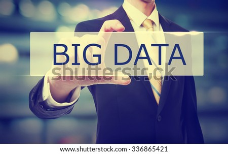 Business man holding Big Data on blurred abstract background   - stock photo
