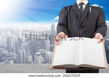business man holding book blank at high building construction site against blue sky with in concept ecology and real estate - stock photo