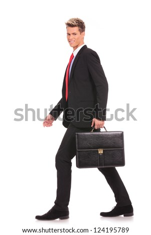 business man holding brief case and walking over white background - stock photo
