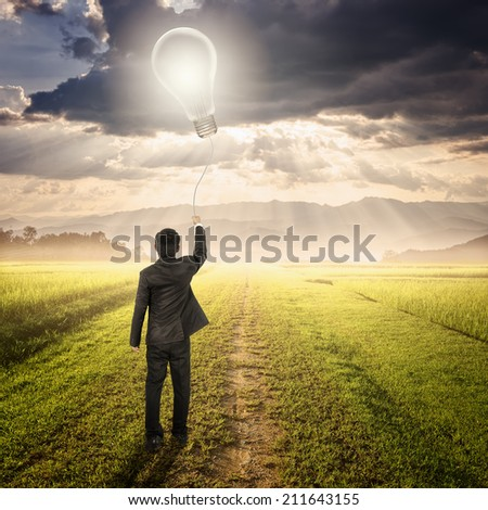 Business man holding bulb balloon in Way on fields and sunset  - stock photo