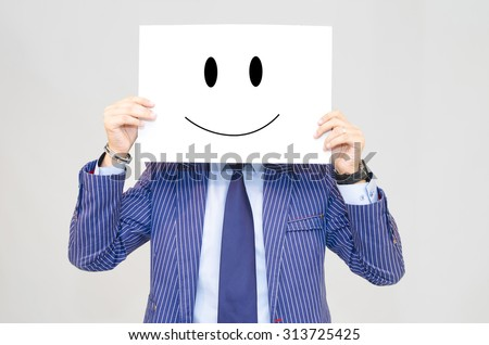 Business man holding card with happy face isolated on grey background - stock photo
