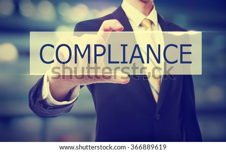 Business man holding Compliance on blurred abstract background   - stock photo