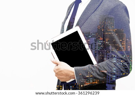 business man holding computer tablet double exposure with building - stock photo