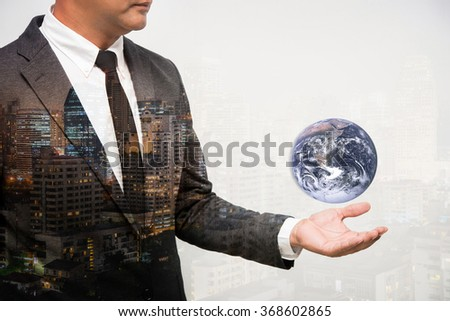 Business Man Holding Earth globe double exposure with building. Elements of this image furnished by NASA - stock photo