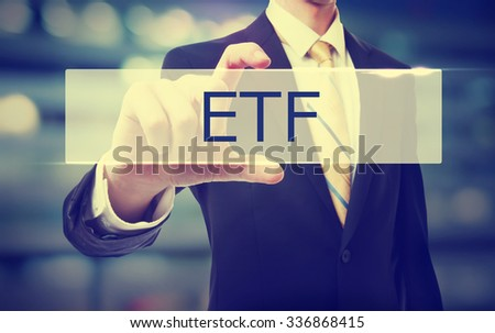Business man holding ETF on blurred abstract background   - stock photo