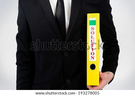 Business man holding folder with solution - stock photo