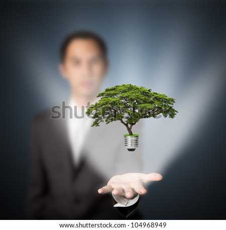 business man holding green energy concept light bulb in hand - stock photo