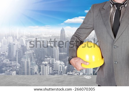 business man holding helmet at high building construction site against blue sky with in concept ecology and real estate