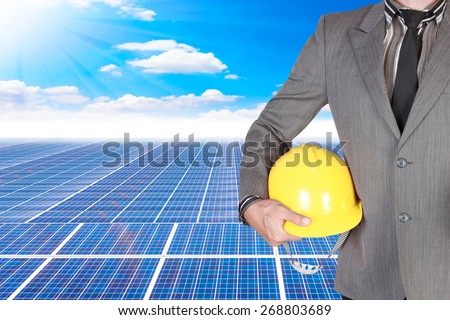 business man holding helmet for working at solar energy power plant against beautiful sky with in concept ecology - stock photo