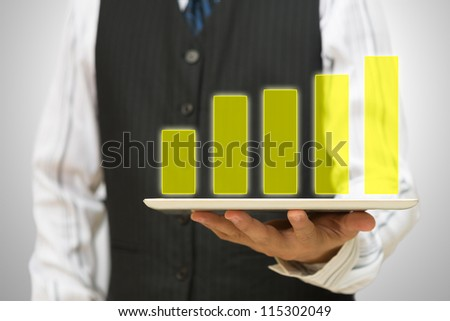 Business man holding Holographic bar graph on tablet pc - stock photo