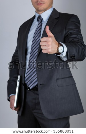 Business man holding laptop and showing thumbs up over gray background. Business success concept - stock photo