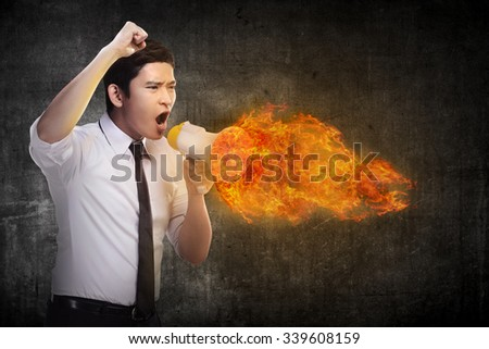 Business man holding megaphone in fire and shouting with furious - stock photo