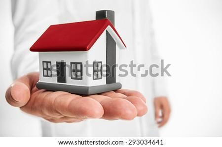 Business man holding model house - stock photo