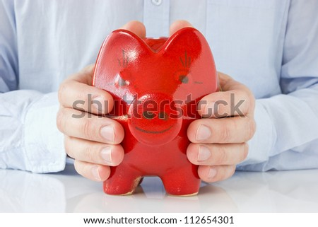 Business man holding piggy bank , concept for money protection - stock photo