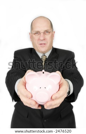 Business man holding Piggy Bank in front of him - stock photo