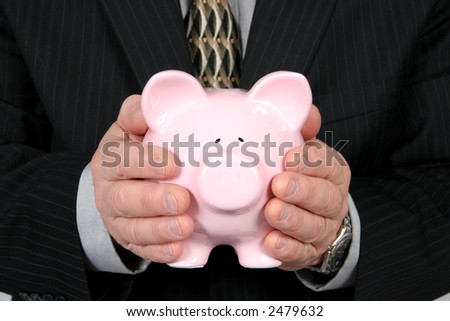 Business man holding Piggy Bank in front of him, taken closeup - stock photo
