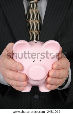 Business man holding Piggy Bank in front of him taken closeup - stock photo
