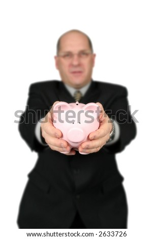 Business man holding Piggy Bank in front of him with focus on piggy bank - stock photo