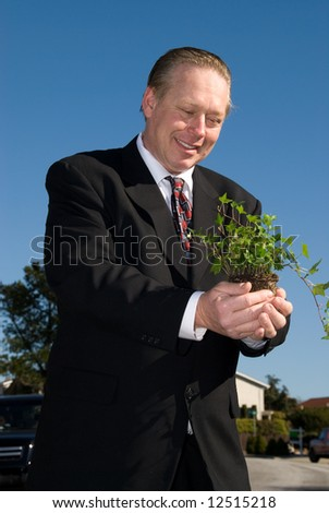 Business man holding plant. - stock photo