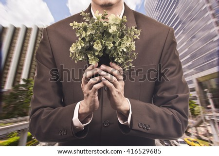 Business man holding plant - environmental concept