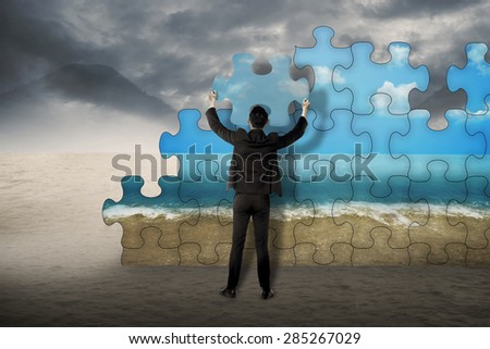 Business man holding puzzle to assembly change situation from desert to sea shore