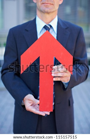 Business man holding red arrow pointing towards his face - stock photo
