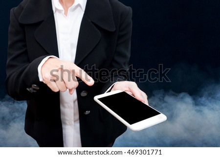 business man holding smart phone with smoke in background