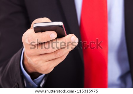 Business man holding smartphone - close up picture - stock photo