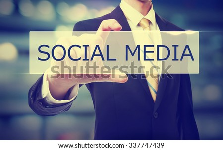 Business man holding Social Media on blurred abstract background   - stock photo