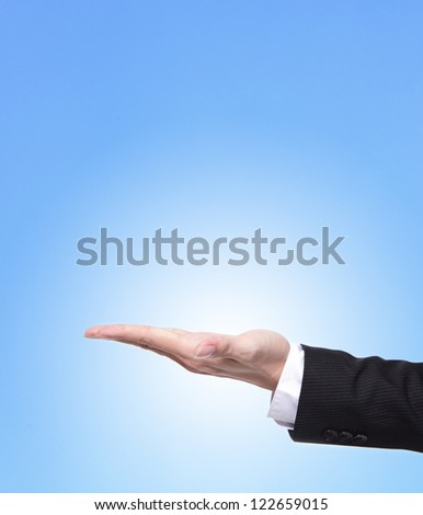 Business man holding something on his hand close up isolated on blue background, copy space area in the image is great for you - stock photo