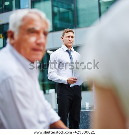 Business man holding speech to his team outdoors