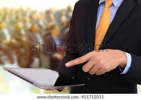 business man holding tablet and using touchpad at meeting with business people background. - stock photo