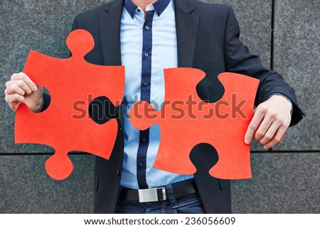 Business man holding two oversized red jigsaw puzzle pieces - stock photo