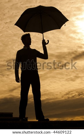 Business man holding umbrella against sunset - stock photo