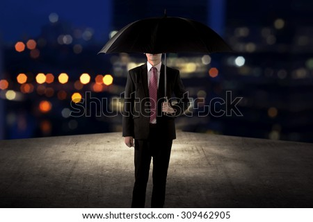 Business man holding umbrella standing on the rooftop of the building at night time - stock photo