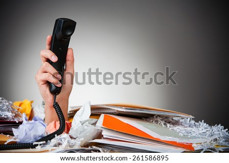 Business: Man Holding Up Phone From Pile Of Paper - stock photo