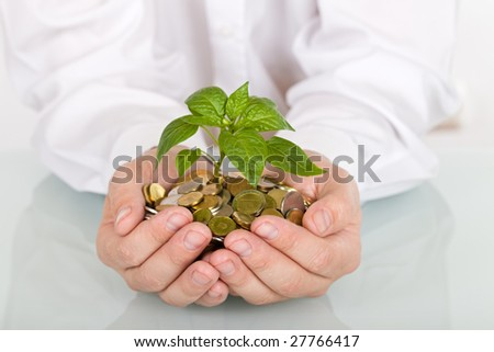 Business man holding young plant rising from a pile of coins - good investment and savings concept - stock photo