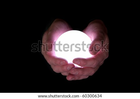 Business man holds glowing crystal ball against black background - stock photo