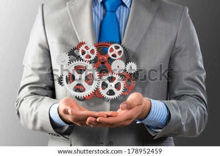 business man holds up a mechanism of gears, concept of ready solutions - stock photo