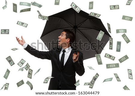 Business man in a money rain storm holding his hand out