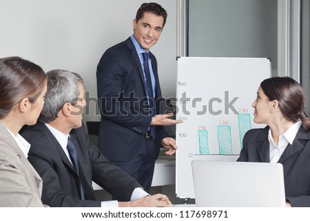 Business man in a office presentation showing sales data on a whiteboard - stock photo