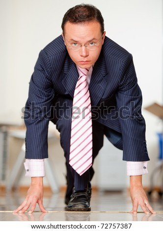 Business man in a position ready to race at the office - stock photo