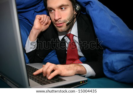 business man in bed with laptop and headset - stock photo