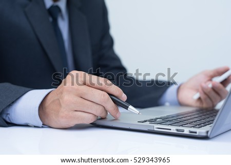 Business man in black suit holding ballpoint pen working on laptop  computer and using mobile smart phone in office room, close up, online working concept.