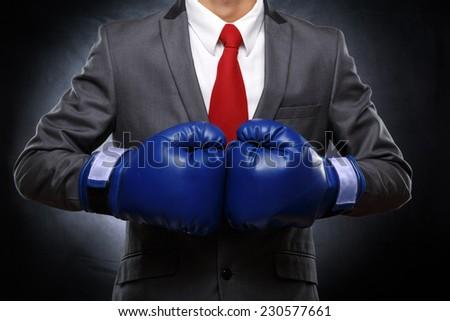 Business man in blue gloves on dark background . Detail of torso. - stock photo