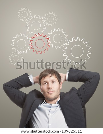 Business man in chair thinking cogwheels over his head - stock photo