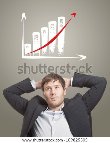 Business man in chair thinking with a rising chart diagram over his head - stock photo