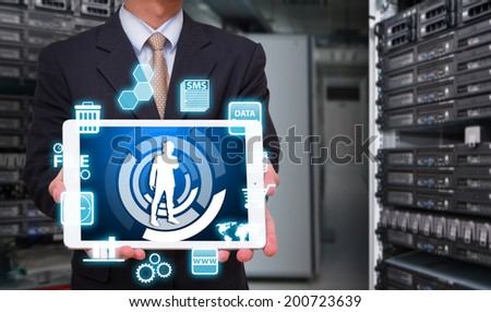 Business man in data center room and icon control  - stock photo