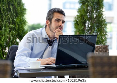 Business man in deep thought with laptop and documents on table