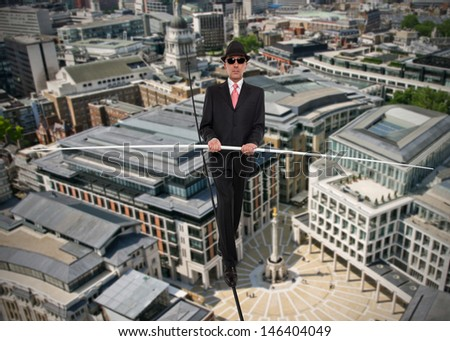 Business man in equilibrium on a rope over a city - stock photo